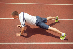 Sports man doing push-ups on running track Stock Photo