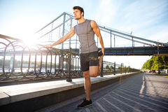 Sports man doing stretching leaning against the bridge railing Royalty Free Stock Photo
