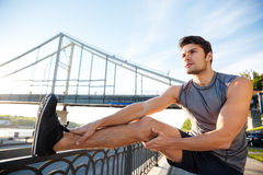 Sports man doing stretching leaning against the bridge railing Royalty Free Stock Image