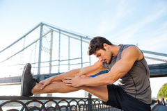 Sports man doing stretching leaning against the bridge railing Royalty Free Stock Photography