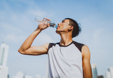 Sports man drinking water after exercising on background of public park Royalty Free Stock Image
