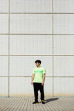 Sports man in a green T-shirt. Full length portrait of young athletic man in bright sportswear standing against white brick wall background at sunny day, ready stock photography