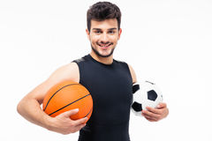 Sports man holding basketball and soccer ball Royalty Free Stock Photo