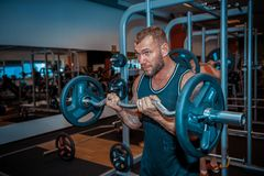 Sports man lifts weights in the gym. stock photography