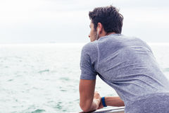Sports man looking at sea outdoors Royalty Free Stock Images