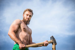 Sports man with a naked torso with beard, scores a wooden pole with a sledgehammer against the blue sky background Royalty Free Stock Photography