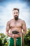 Sports man with a naked torso with beard, smile and standing against the blue sky green natural background with a hammer in hi Royalty Free Stock Photography