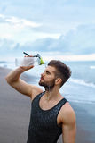 Sports Man Pouring Water Over Face After Workout At Beach. Stock Image