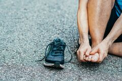 Sports Man Runner With Injured Foot While Training On The Asphalt Road . Healthcare, Medicine And People Concept. Stock Photos