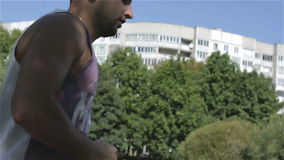 The sports man is running in a tree`s shadow. Side view. stock footage