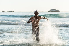 Sports man running in water. Topless, athletic, muscular and healthy black man running along the beach, splashing water during sunset Royalty Free Stock Image