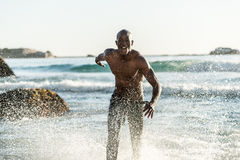 Sports man running in water. Topless, athletic, muscular and healthy black man running along the beach, splashing water during sunset Stock Photography