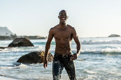 Sports man running in water. Topless, athletic, muscular and healthy black man running along the beach, splashing water during sunset Stock Images