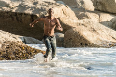 Sports man running in water. Topless, athletic, muscular and healthy black man running along the beach, splashing water during sunset Royalty Free Stock Photography
