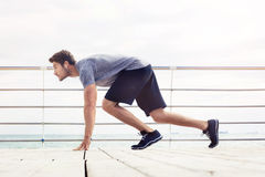 Sports man in start position outdoors. Portrait of a sports man in start position outdoors. Reading for run Stock Photo