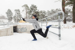 Sports man stretching leg at fence in winter Stock Photography