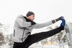Sports man stretching leg at fence in winter Stock Photo