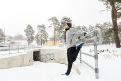 Sports man stretching leg at fence in winter Stock Image