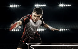 Sports man tennis-player on black background. Young sports man tennis-player in play on black background with lights Stock Photos