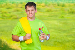 A sports man with towel holding bottle of water Royalty Free Stock Image