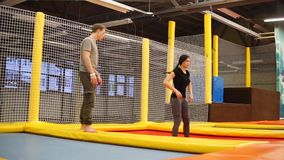 The coach looks at how his student jumps on trampolines, she trains. The sports man trains his podgoo with jumping on trampolines, the lady performs the basics stock video