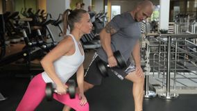 Sports man and woman in tattoo train muscles of arms of dumbbells. In gym young strong people strain limbs with weights to develop endurance stock video footage