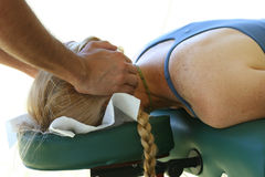 Sports Massage. Male massage therapist working on a client's neck. Woman is face down on massage table Stock Photos