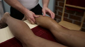 Sports massage - Leg massage - Physical therapist doing massage of calfs, applying strong finger pressure. Toned image stock video footage