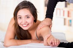 Sports massage. Massage therapist massaging shoulders of a female smiling athlete, working with Trapezius muscle.  Stock Photos