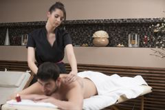Sports massage. Massage therapist massaging shoulders of a male. Athlete, working with Trapezius muscle Stock Photography