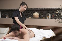 Sports massage. Massage therapist massaging shoulders of a male. Athlete, working with Trapezius muscle Royalty Free Stock Images