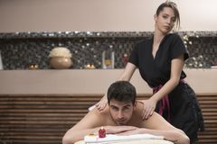 Sports massage. Massage therapist massaging shoulders of a male. Athlete, working with Trapezius muscle Stock Photos