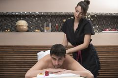 Sports massage. Massage therapist massaging shoulders of a male. Athlete, working with Trapezius muscle Stock Images