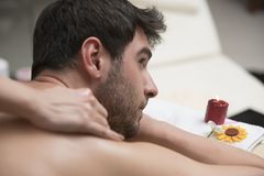 Sports massage. Massage therapist massaging shoulders of a male. Athlete, working with Trapezius muscle Royalty Free Stock Photography