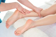 Sports Massage. Massage therapist working with patient, massagin. G his calves. Close-up image Royalty Free Stock Photography