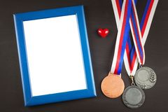 Sports medals on a wooden background. Collection of medals for the winners. Awards in sports. Royalty Free Stock Photo