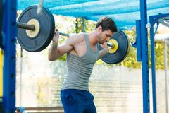 Sports model exercising outside as part of healthy dumbbells. Male sports model exercising outside as part of healthy lifestyle Stock Image