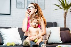 Sports mom with her baby at home. Sports mom eating apple sitting with her baby on the couch at home royalty free stock photos