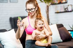 Sports mom with her baby at home. Sports mom drinking water after the training sitting with her baby on the couch at home stock photos