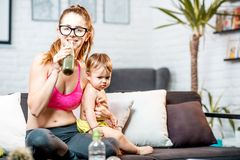 Sports mom with her baby at home. Sports mom drinking fresh green smoothie after the training sitting with her baby boy on the couch at home stock photos
