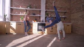 Sports mother doing flips in front of her daughters in kitchen in slow motion stock video