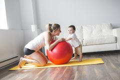 Sports mother is engaged in fitness and yoga with a baby at home royalty free stock photography