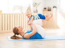 Sports mother is engaged in fitness and yoga with baby at home royalty free stock images