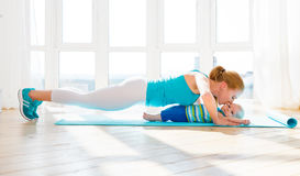 Sports mother is engaged in fitness and yoga with baby at home royalty free stock photos