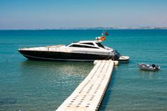 Sports motor yacht at the pier. Beautiful boat on a background of blue sky and sea. Stock Image