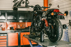A sports motorcycle at a service station. The bike is on the lift during the repair royalty free stock photo