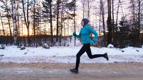 Sports muslim girl on a run in the winter forest. Sun stock video