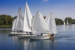 Sports naviguant dans un bon nombre de petits bateaux blancs Photographie stock