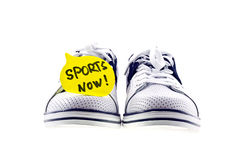 Sports now. White and navy blue sneakers with a speech bubble paper note isolated on white stock images