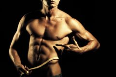 Sports nutrition. Male and tape measure. Sports nutrition. Closeup of young naked man with sexual strong muscular beautiful tan body showing finger on yellow Royalty Free Stock Photos